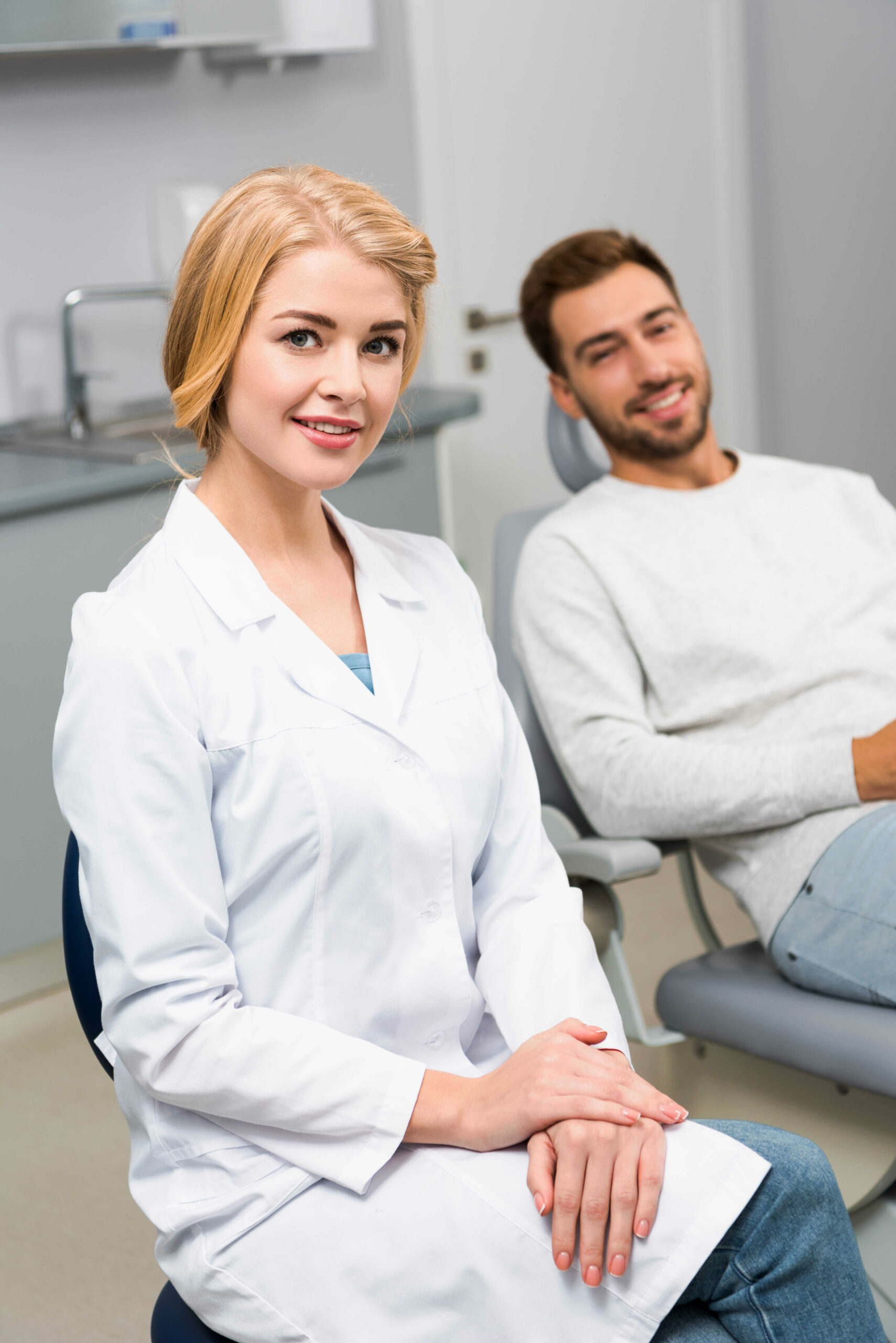 happy-female-dentist-and-handsome-young-client-looking-at-camera-in-dentist-office-in-chicago