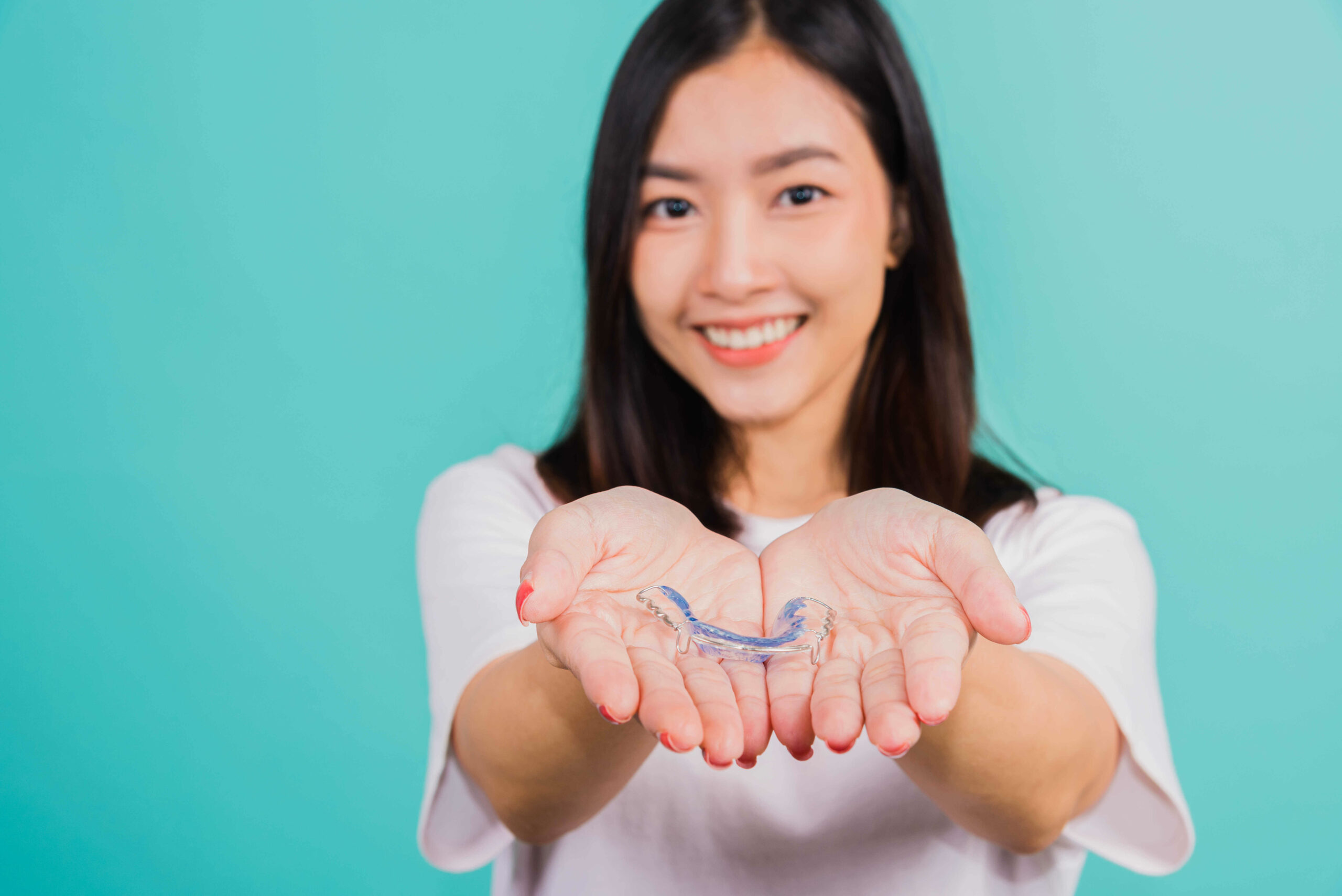 portrait-young-asian-beautiful-woman-smiling-holding-silicone-orthodontic-retainers-for-teeth-on-hand-palm-in-chicago