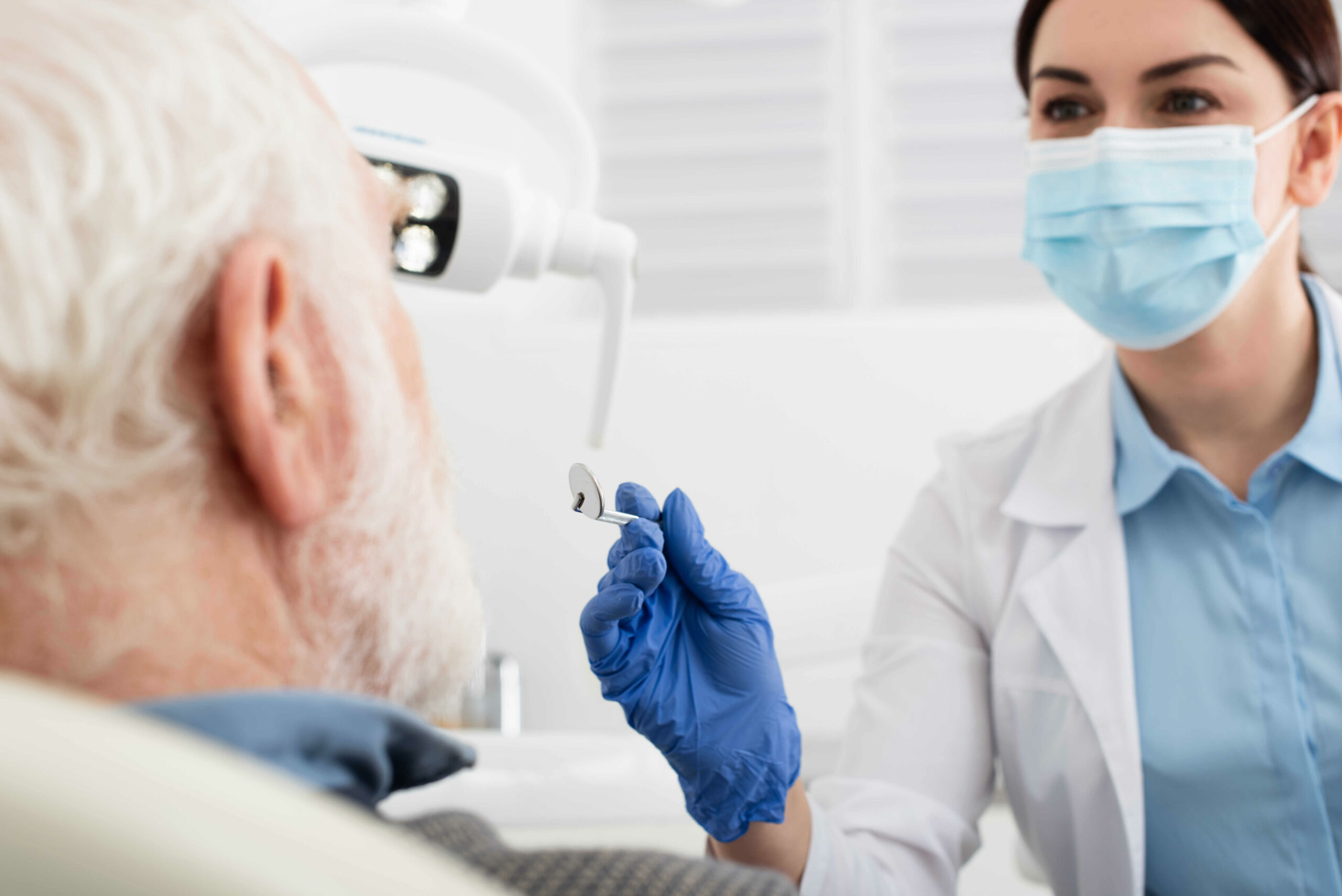 senior-man-having-teeth-examination-by-dentist-in-latex-gloves-with-mirror-in-clinic-in-chicago