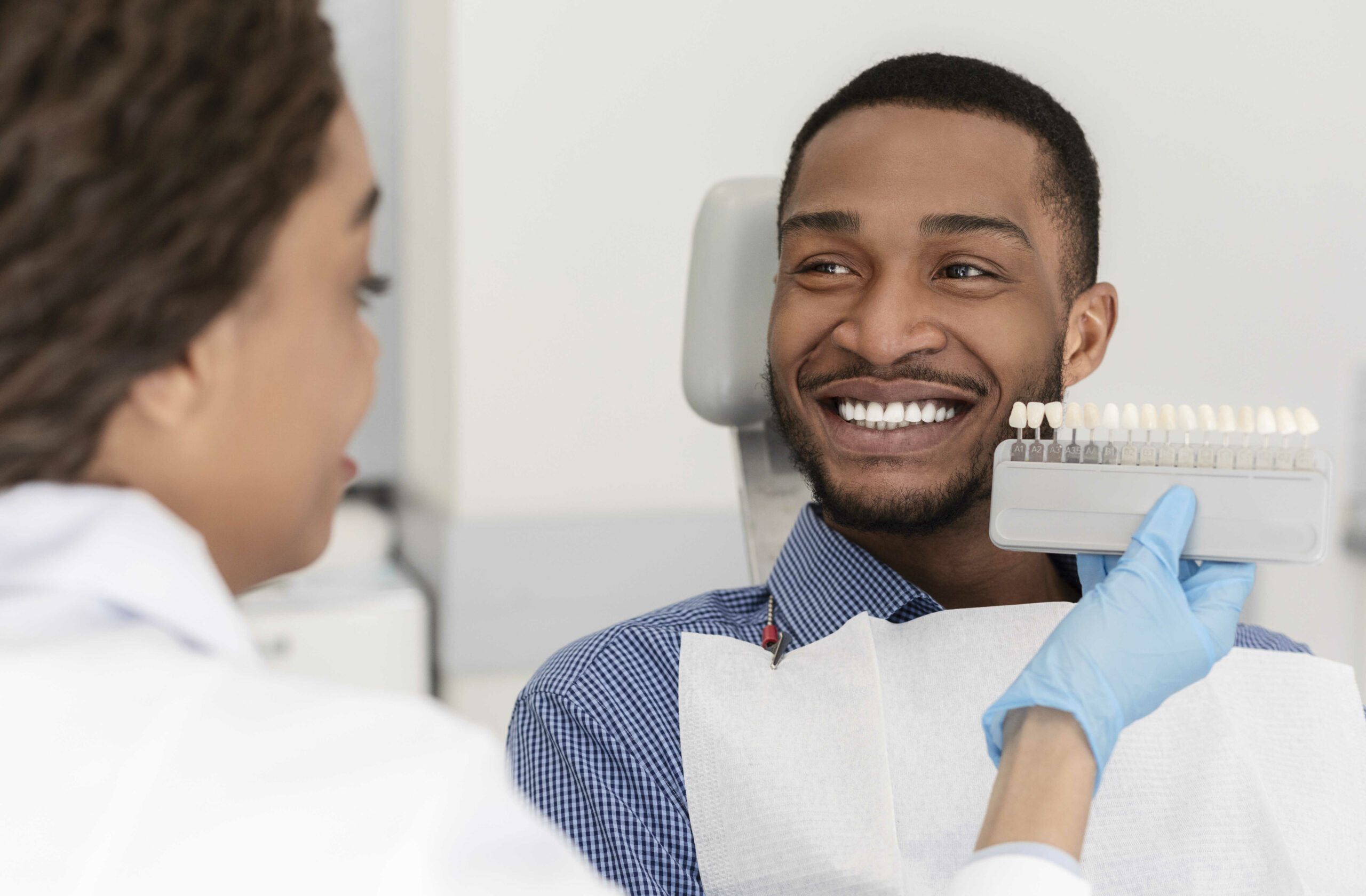 Cheerful african patient and dentist choosing filling shade in Chicago